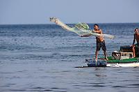 A fishermen casts a net off the coast of Cuba.