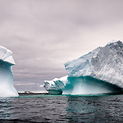 An iceberg seems to be carved in two, but is connected underwater, at Two Hummock Island on the Antarctic Peninsula.
