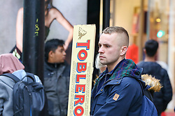© Licensed to London News Pictures. 23/12/2018. London, UK. A man with a large Toblerone chocolate waiting for a bus on Oxford Street. Last minute Christmas shoppers take advantage of pre-Christmas bargains in London's Oxford Street. Fewer shoppers have been reported shopping in Britain's high streets as online sales increase. Photo credit: Dinendra Haria/LNP