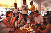TOURISM CLUBBING, Ibiza. Family eating lunch, tapas, Ibiza & Formentera, Baleares islands, Spain, Mediterranean, Europe. Popular holiday resort catering mainly for european tourists. Summer high season, April until September. Well known for 24 hour nightclubbing, package holidays, jet set, all night raves, dancing, techno clubs, drag queens & gay scene, discotheques, speciality theme nights, soapsuds, foam parties, espuma, la mousse. Attractions include shopping, beaches, watersports, boating..