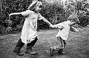"""A brother and sister run through the back garden of their South London home. We see the younger sibling - a boy of three leading his big sister by the hand in some sort of follow-my-leader game. He pulls hard to tow the girl along who wears Wellington boots that are too large for her and they both hold out their arms for stability. From a personal documentary project entitled """"Next of Kin"""" about the photographer's two children's early years spent in parallel universes. Model released."""