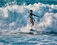 Surfer catching a wave at Sunset Beach. Image taken with a  Nikon N1 V3 camera and 70-300 mm VR lens (ISO 200, 300 mm, f/5.6, 1/1000 sec). Burst mode on this camera is great!