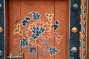 A brightly painted flower on a door. This is probably a stylised lotus flower. Lobesa, Druk Yul, Bhutan.   13 November 2007