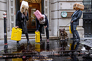 Extinction Rebellion Climate Change activists dressed in City suits, vomit 'oil' outside the Baltic Exchange, home to the International Chamber of Shipping (ICS) who, according to environmentalists, are co-sponsoring the IMO's non-reglation, thereby allowing fossil fuel emissions by the shipping industry, on 16th November 2020, in London, England. 'Scrubbers' then appeared to metaphorically clean-up the mess left on the pavement before City of London Police officers arrived to re-open the street during this, the second lockdown during the Coronavirus pandemic.