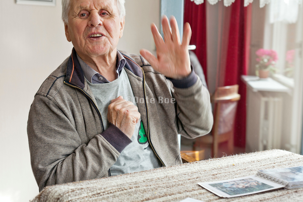 happy elderly man sitting at the table with photo album