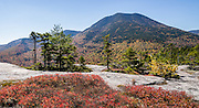 "For views of fall leaf colors and Mount Passaconaway (4043 ft) in White Mountain National Forest, hike the rocky UNH Loop Trail (4.8 miles, 1600 feet gain) on Hedgehog Mountain in the Sandwich Range Wilderness in New Hampshire, USA. The peak intensity of autumn foliage color here is around the first week of October. Find the trailhead parking area marked ""Downes Brook - UNH - Mt. Potash Trails"" along Kancamagus Highway (NH Route 112) across from Passaconaway Campground and Passaconaway Historic Site. The White Mountains (a range in the northern Appalachians) cover a quarter of the state of New Hampshire. The panorama was stitched from 2 overlapping photos."