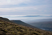 A line of wind turbines in the horizon on the top of Rhigos Hill Pass in the Cynon Valley, Rhondda Cynon Taf, South Wales, United Kingdom. There are 76 turbines creating a 228M Renewable Energy Wind Farm.  The view is from Pen Y Fan Mountain and looks over the Rhondda Valley on a  misty day.