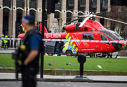 © Licensed to London News Pictures. 22/03/2017. London, UK. An air ambulance and armed Police at the scene of suspected terrorist attack near Houses of Parliament in Westminster, London. Photo credit: Ben Cawthra/LNP