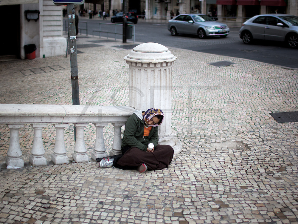 A woman from Romania seats on the floorat Praça dos Restauradores for begging.This photograph is part of a body of work about Lisbon, feelings, affections and loneliness. Is about a city depressed by the crisis, but even so, tolerant and cosmopolitan. This part of Lisbon, the old town near the river Tejo (Tagus), with his deep character, where local people meets foreigners and alternative ways of life mixes with shamefaced poverty, is sublime by its peculiar light.