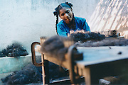 In the town of Eluru in the state of Andhra Pradesh a young girl works at getting the strands of temple hair all the same length.