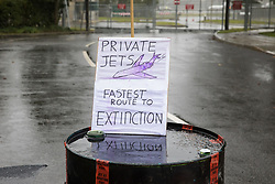 A sign displayed by Extinction Rebellion climate activists on a fuel barrel outside an entrance to Farnborough Airport is pictured on 2nd October 2021 in Farnborough, United Kingdom. Activists blocked three entrances to the private airport to highlight elevated carbon dioxide levels produced by super-rich passengers using private jets and 'greenwashing' by the airport in announcing a switch to sustainable aviation fuel (SAF).
