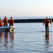NLD/Naarden/20060115 - Politie en brandweer Naarden met boot rukken uit naar het Naarderbos waar iets in het water te zien is, later blijkt dit een door de stroming gevormde zandbank, meer, water, golven, naardermeer, waadpakken,