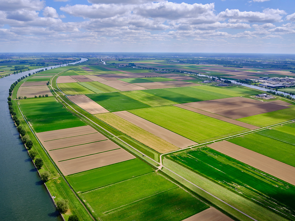 Nederland, Noord-Brabant, Gemeente Waspik, 14-05-2020; Overdiepsche polder (Overdiepse Polder). In het kader van het programma 'Ruimte voor de Rivier' (bescherming tegen hoogwater door rivierverruiming), is de dijk langs de Bergsche Maas (links in beeld) verlaagd. Bij hoogwater kan de Overdiepse polder overstromen. De boerderijen in de polder zijn gesloopt en verplaatst naar de dijk van het Oude Maasje. De nieuwe boerderijen met bijgebouwen staan op terpen.<br /> Depoldering of Overdiep Polder, farms are relocated and built on mounds. This makes it possible for the river to overflow the polder in case of heigh waters.<br /> <br /> luchtfoto (toeslag op standard tarieven);<br /> aerial photo (additional fee required);<br /> copyright foto/photo Siebe Swart