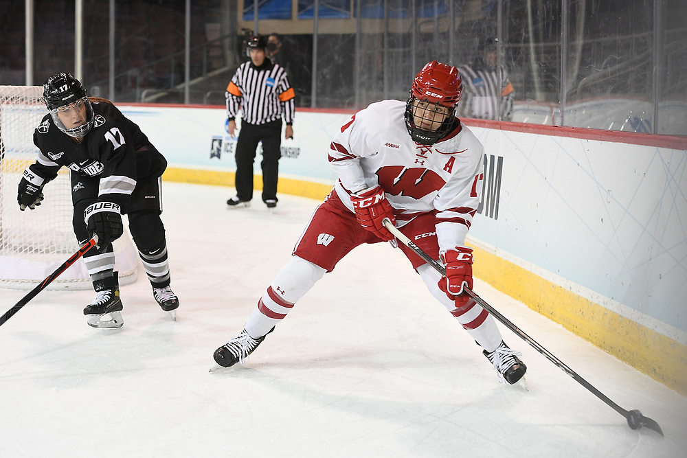 ERIE, PA - MARCH 16: Britta Curl #17 of the Wisconsin Badgers controls the puck under pressure from Brooke Becker #17 of the Providence Friars in the first period during the NCAA Tournament Quarterfinals game at the Erie Insurance Arena on March 16, 2021 in Erie, Pennsylvania. (Photo by Justin Berl)