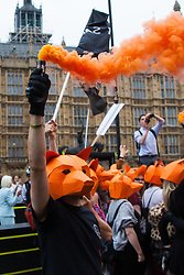 """Westminster, London, July 14th 2015. Hundreds of animal rights activists and members of hunt saboteur groups gather outside Parliament to """"Fight For THe Fox"""" as Paliament discusses an amendment to the bill outlawing fox hunting that could see the sport return to the British countryside. PICTURED: Wearing fox masks, campaigners block the street outside Parliament."""