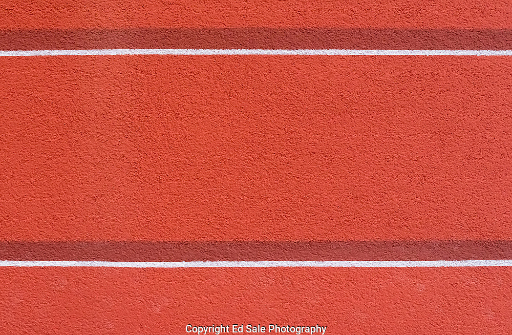 A red wall in Bonasollo, Italy with two white horizontal lines imparts simplicity and tranquility