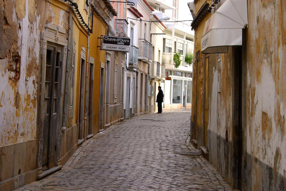 A lone shopper studies a window in this street scene, Tavira, Algarve Portugal