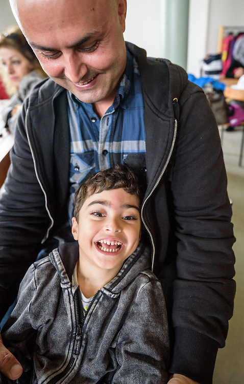 """13 August 2016, Norrbyskär, Umeå, Sweden: Ahuora (child), and his father Hussein are from Iran, but they now live in Umedalen, in Umeå, Sweden, where they have been staying for the last 5 months. Here they are, enjoying their day at the Kul-Tur Fest (""""Culture Festival""""). The event, which attracted hundreds of people, set out to offer a meeting place for Swedish culture and new forms of cultural expression, and featured baking competitions, dance workshops, book discussions, fingernail painting and music, among other things."""