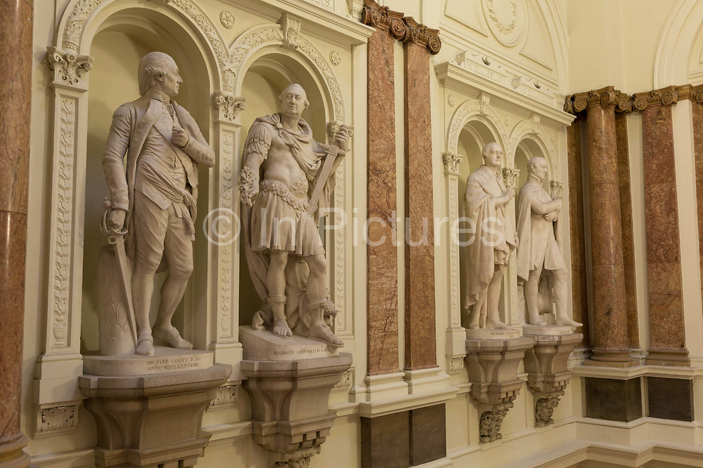 The statues of Sir Eyre-Coote, K.B. by Thomas Banks 1788 and   <br /> Marquis Cornwallis, K.G. by John Bacon, Senior 1791 in the Gurkha Stair in the former India Office, which was part of the Foreign and Colonial Office now the Foreign and Commonwealth Office, Whitehall, London. on 17th September 2017, in Whitehall, London, England. The main Foreign Office building is in King Charles Street, and was built by George Gilbert Scott in partnership with Matthew Digby Wyatt and completed in 1868 as part of the new block of government offices which included the India Office and later 1875 the Colonial and Home Offices. George Gilbert Scott was responsible for the overall classical design of these offices but he had an amicable partnership with Wyatt, the India Office's Surveyor, who designed and built the interior of the India Office.
