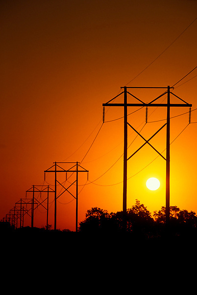 Stock photo of a silhouette of a group of power poles and lines at sunset