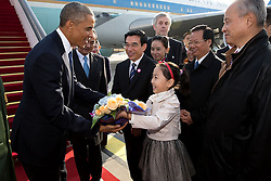 President Barack Obama is presented with a bouquet of flowers by a young girl upon his arrival at Beijing Capital International Airport in Beijing, China, Nov. 10, 2014. (Official White House Photo by Pete Souza)<br /> <br /> This official White House photograph is being made available only for publication by news organizations and/or for personal use printing by the subject(s) of the photograph. The photograph may not be manipulated in any way and may not be used in commercial or political materials, advertisements, emails, products, promotions that in any way suggests approval or endorsement of the President, the First Family, or the White House.