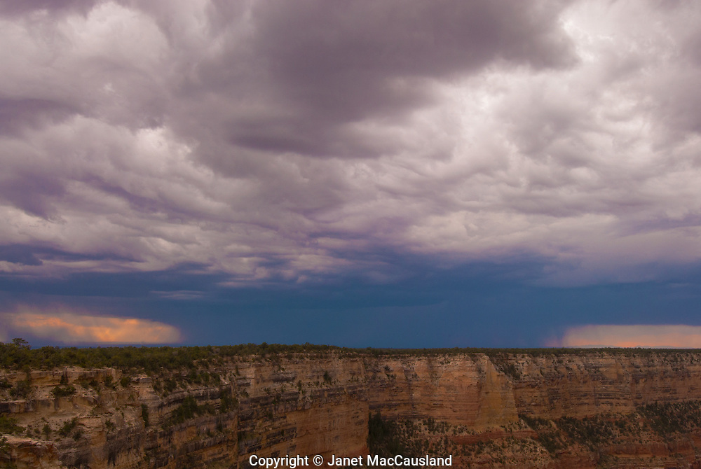 A rain storm descends on the north side of the banks of the Grand Canyon near sunset.