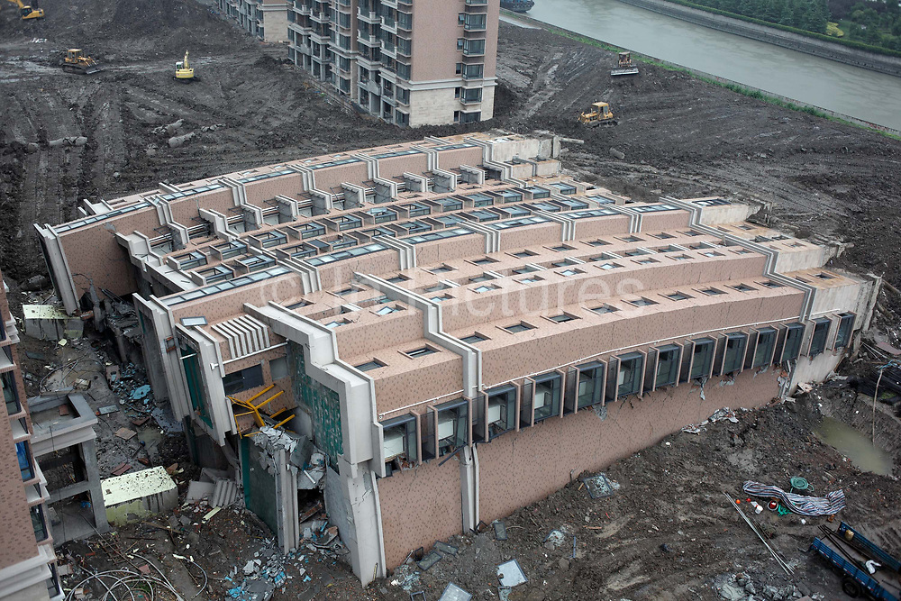 """A view of a collapsed apartment building at the """"Riverside Lotus"""" developement in Shanghai, China on 29 June 2009.  Frenzied construction pace throughout China's ongoing building boom, the largest in recorded history, has left much to be wondered about safety and quality, as the toppling of this nearly finished 11 story apartment complex demonstrates."""