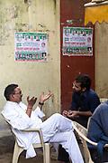 Two men talk by a demonstration near the Jantar Mantar, New Delhi, India