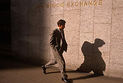 A young man strides past the wall and name of the London Stock Exchange in the City of London. Walking fast past this financial institution, we see the young man's shadow on the wall beneath the name on the exterior wall. Three years after the so-called Big Bang in 1986 , this location at the old Stock Exchange Tower  became redundant with the advent of the Big Bang, which deregulated many of the Stock Exchange's activities as it enabled an increased use of computerised systems that allowed dealing rooms to take precedence over face to face trading. Thus, in 2004, the House moved to a brand new headquarters in Paternoster Square, close to St Paul's Cathedral.