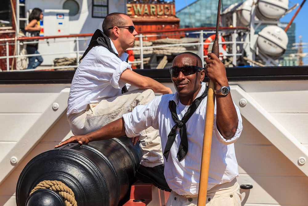 Baltimore, MD, USA - June 16, 2012: Sailors take a break wth a cannon at the Inner Harbor in the City of Baltimore, Maryland.