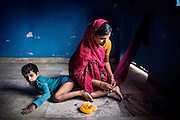 Rachi, 7, a disabled girl affected by microcephaly and myoclonic epilepsy, is being restrained with a cord to her ankle by her mother Jyoti Yadav, 34, a '1984 Gas Survivor', in order to keep her from wandering off on her own and being at risk of abuse and danger, while inside their home near Saifiya College, in Bhopal, Madhya Pradesh, central India.