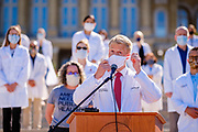 01 AUGUST 2020 - DES MOINES, IOWA: Dr. AUSTIN BAETH takes off his face mask before speaking at the Iowa State Capitol Saturday. About 50 doctors, medical professionals, and public health professionals from across Iowa came to the State Capitol to demand that Iowa Governor Kim Reynolds impose a mask mandate to control the spread of the coronavirus (SARS-CoV-2). Despite the continued spread of the coronavirus and rapidly increasing infection rate for COVID-19, the Governor has refused to impose a mask mandate or close businesses. For the week ending Saturday, Aug. 1, Iowa reported new 2,736 new cases of COVID-19.            PHOTO BY JACK KURTZ