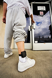 Aug 01, 2006 - Santa Ana, California, USA - Wearing an electronic ankle monitor, a teenage offender enters a county parole facility in Santa Ana, CA. An ankle monitor is a device that individuals under house arrest are often required to wear. In timed intervals, the ankle monitor sends a radio frequency or GPS signal to a receiver. If an offender wanders outside his or her allowed range, the police will be notified. Ankle monitors are designed to be tamper-resistant and can often alert police to tampering attempts. (Credit Image: © Spencer Grant/ZUMA Press)