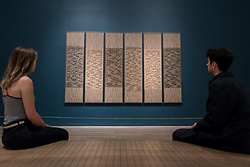 """© Licensed to London News Pictures. 09/10/2018. LONDON, UK. Visitors view """"Six Prayers"""", 1966-7, by Anni Albers.  Preview of the UK's first exhibition of works by German artist Anni Albers at Tate Modern who used the ancient art of hand-weaving to produce works of modern art.  Over 350 of her artworks from major collections from Europe and the US are on show 11 October to 27 January 2019.  Photo credit: Stephen Chung/LNP"""