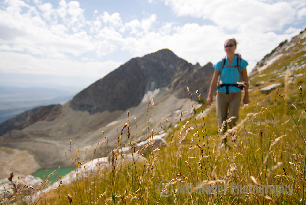 A young woman hikes above Timberline Lake in Grand Teton National Park, Jackson Hole, Wyoming.