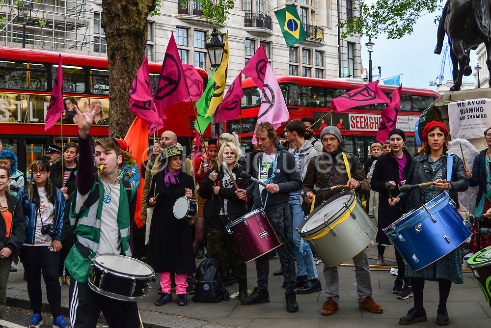 Drummers play at Extinction Rebellions Carn-evil of Chaos Fashion Parade outside the Brazilian Embassy on 1st May 2019 in London, England,UK. Climate change activist group Extinction Rebellion accuse the Brazilian government of wrecking biodiversity of the Amazon rainforest  for financial gain and to halt the contruction of a motorway through the forest.