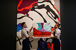 "© Licensed to London News Pictures. 27/09/2019. London, UK. Technicians hold Andy Warhols's artwork titled ""Vesuvius"" - Est - £280,000 - £350-000 in front of Kaws' artwork titled ""The Final Machine"" Est - £5000,000 - £700,000 during the preview of Sotheby's Frieze Week Contemporary Art Sale. The auction will take place on 3rd October 2019.  Photo credit: Dinendra Haria/LNP"
