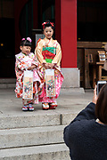 mother photographing little children in festive kimono celebrating Shichi Go San Japan