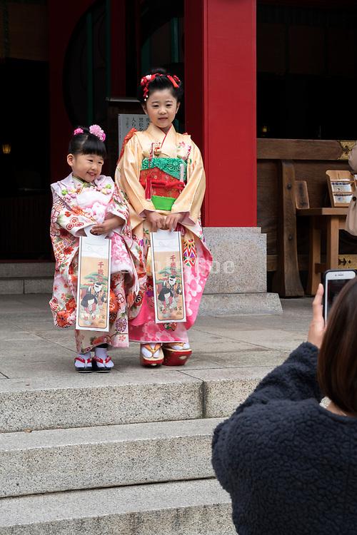 mother photographing little children in festive kimono celebrating Shichi Go San Japan