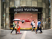 "23 AUGUST 2013 - BANGKOK, THAILAND:    Pedestrians walk past a Louis Vuitton store in Bangkok. Thailand entered a ""technical"" recession this month after the economy shrank by 0.3% in the second quarter of the year. The 0.3% contraction in gross domestic product between April and June followed a previous fall of 1.7% during the first quarter of 2013. The contraction is being blamed on a drop in demand for exports, a drop in domestic demand and a loss of consumer confidence. At the same time, the value of the Thai Baht against the US Dollar has dropped significantly, from a high of about 28Baht to $1 in April to 32THB to 1USD in August.    PHOTO BY JACK KURTZ"