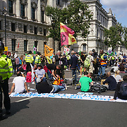 Extinction Rebellion activists blocks Whitehall - Impossible Rebellion Day 2 blocks Whitehall sitin and some locks themselves iinside a box in London, UK, on 2021-08-24.