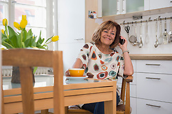 Happy senior woman having a cup of tea and talking on cell phone in kitchen, Munich, Bavaria, Germany