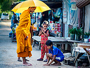 """15 FEBRUARY 2019 - SIHANOUKVILLE, CAMBODIA:  Children prevent alms to a Buddhist monk in a migrant camp in Sihanoukville. Families who live in the shanty town came to Sihanoukville from other Cambodian provinces because of the town's booming economy and construction industry building Chinese resorts and casinos. There are about 80 Chinese casinos and resort hotels open in Sihanoukville and dozens more under construction. The casinos are changing the city, once a sleepy port on Southeast Asia's """"backpacker trail"""" into a booming city. The change is coming with a cost though. Many Cambodian residents of Sihanoukville  have lost their homes to make way for the casinos and the jobs are going to Chinese workers, brought in to build casinos and work in the casinos.     PHOTO BY JACK KURTZ"""