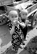 Traditional shaven children eating in market