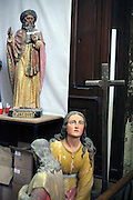 damaged religious sculptures and cross in a side room in church