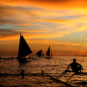 Asian tourists enjoy boat rides during an amazing sunset at White Beach,  Boracay Island, the Philippines on October 3, 2008, Photo Tim Clayton....Asian tourists at White Beach, Boracay Island, the Philippines...The 4 km stretch of White beach on Boracay Island, the Philippines has been honoured as the best leisure destination in Asia beating popular destinations such as Bali in Indonesia and Sanya in China in a recent survey conducted by an International Travel Magazine with 2.2 million viewers taking part in the online poll...Last year, close to 600,000 visitors visited Boracay with South Korea providing 128,909 visitors followed by Japan, 35,294, USA, 13,362 and China 12,720...A popular destination for South Korean divers and honeymooners, Boracay is now attracting crowds of tourists from mainland China who are arriving in ever increasing numbers. In Asia, China has already overtaken Japan to become the largest source of outland travelers...Boracay's main attraction is 4 km of pristine powder fine white sand and the crystal clear azure water making it a popular destination for Scuba diving with nearly 20 dive centers along White beach. The stretch of shady palm trees separate the beach from the line of hotels, restaurants, bars and cafes. It's pulsating nightlife with the friendly locals make it increasingly popular with the asian tourists...The Boracay sailing boats provide endless tourist entertainment, particularly during the amazing sunsets when the silhouetted sails provide picture postcard scenes along the shoreline...Boracay Island is situated an hours flight from Manila and it's close proximity to South Korea, China, Taiwan and Japan means it is a growing destination for Asian tourists... By 2010, the island of Boracay expects to have 1,000,000 visitors.