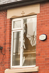 © Licensed to London News Pictures . 08/02/2013 . Salford , UK . Smashed windows on the first floor amongst the damage caused to several houses in a terrace as a consequence of the collision . The scene on Leigh Road where a multi-vehicle pile up killed two , sparked a fire and damaged several cars and houses overnight , causing residents to be evacuated . Greater Manchester Police report seeing a stolen red Audi which they attempted to pursue prior to the crash . Photo credit : Joel Goodman/LNP
