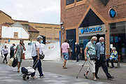 Shoppers, many of whom wearing face coverings, pass a high street site currently being redeveloped on 27th July 2021 in Maidenhead, United Kingdom. A change in rules on commercial-to-residential conversions with effect from 1st August will facilitate the quick conversion of vacant shops and businesses into residential properties by landlords and developers.