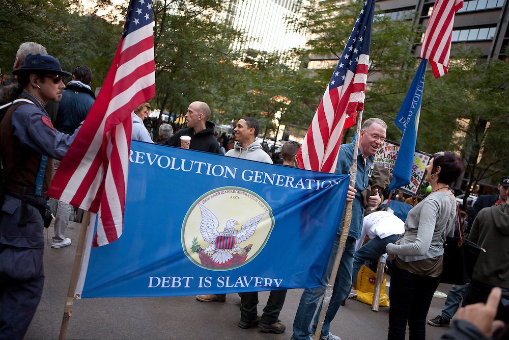 """Men from the New American Regeneration Party hold a banner reading """"Revolution generation debt is slavery""""."""