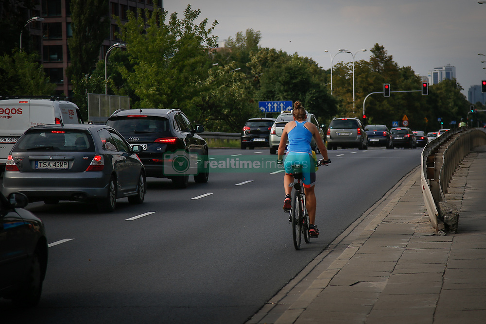 August 4, 2017 - Warsaw, Poland - A woman is seen cycling on a busy road in Warsaw, Poland on 4 August, 2017. (Credit Image: © Jaap Arriens/NurPhoto via ZUMA Press)